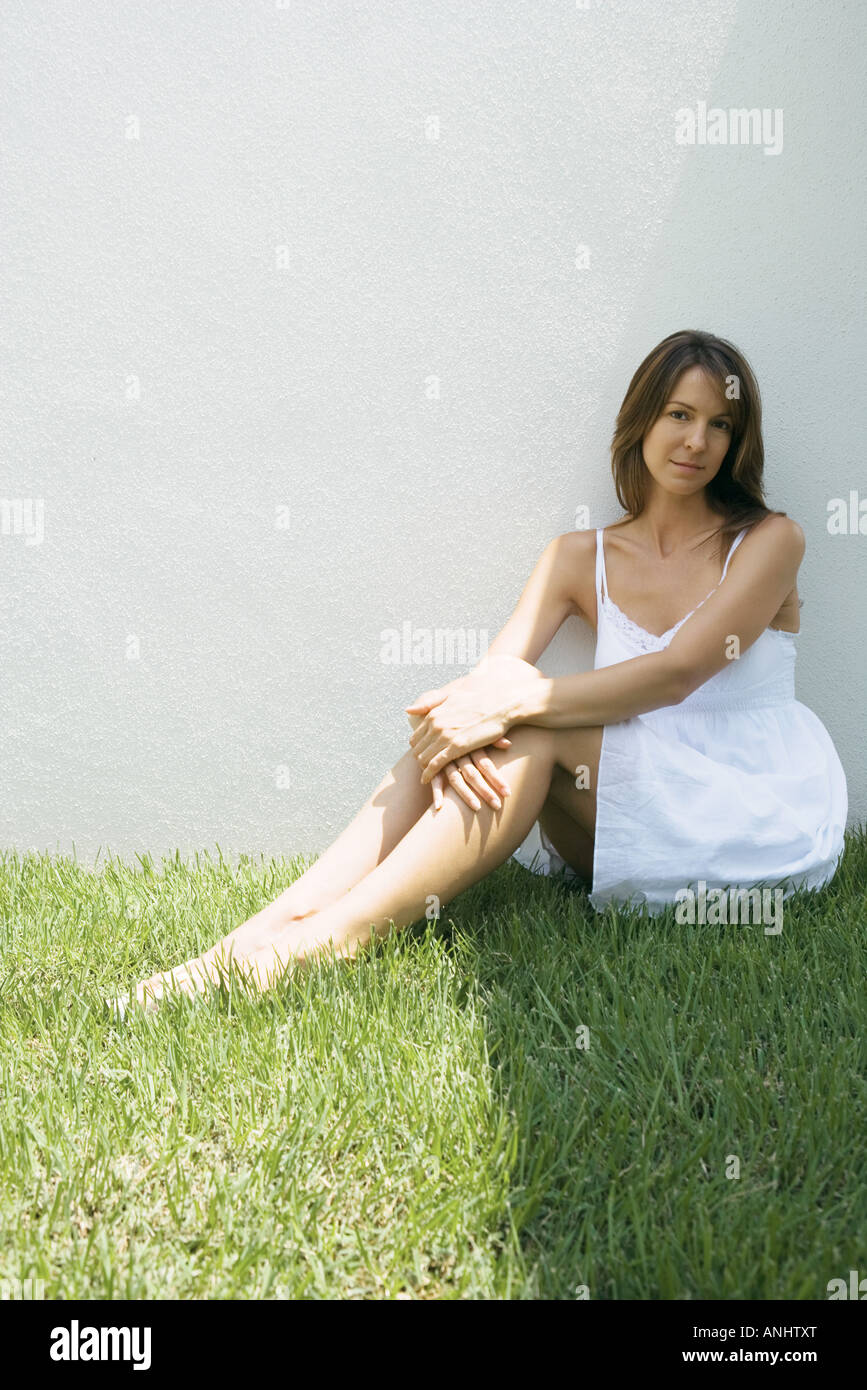 Woman in sundress sitting on grass, smiling at camera, full length - Stock Image