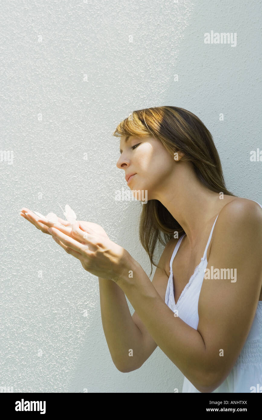 Woman holding fake butterflies on hand - Stock Image