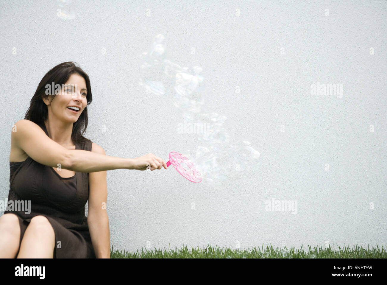 Woman making bubbles with bubble wand - Stock Image