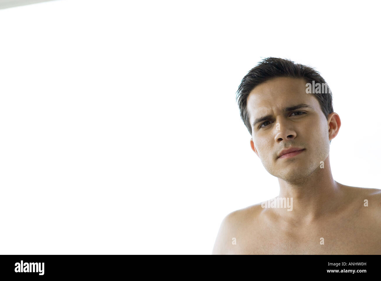 Barechested young man, looking at camera, head and shoulders - Stock Image