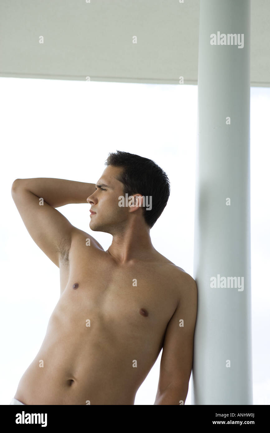 Barechested young man, hand behind head, looking away, waist up - Stock Image
