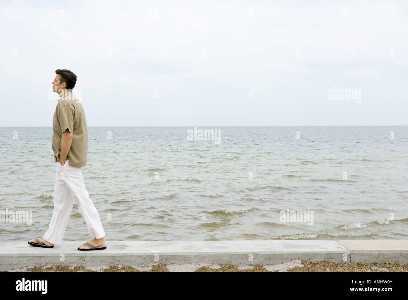 Man walking along low wall by ocean, hands in pockets, full length - Stock Image
