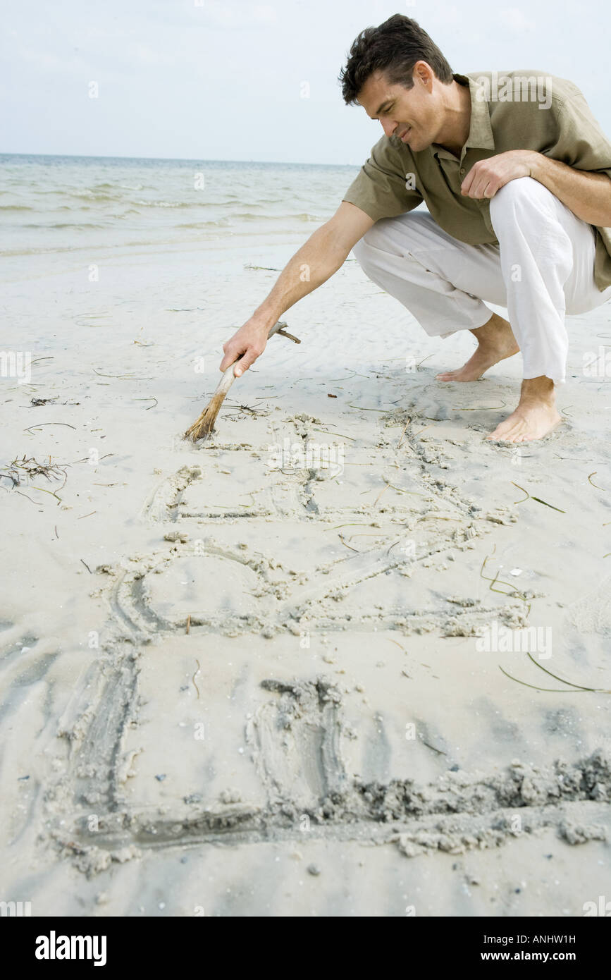 Barefoot man writing word 'free' on beach with stick - Stock Image