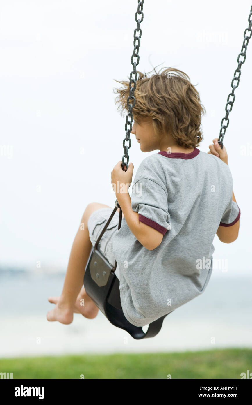 Barefoot boy on swing, rear view - Stock Image