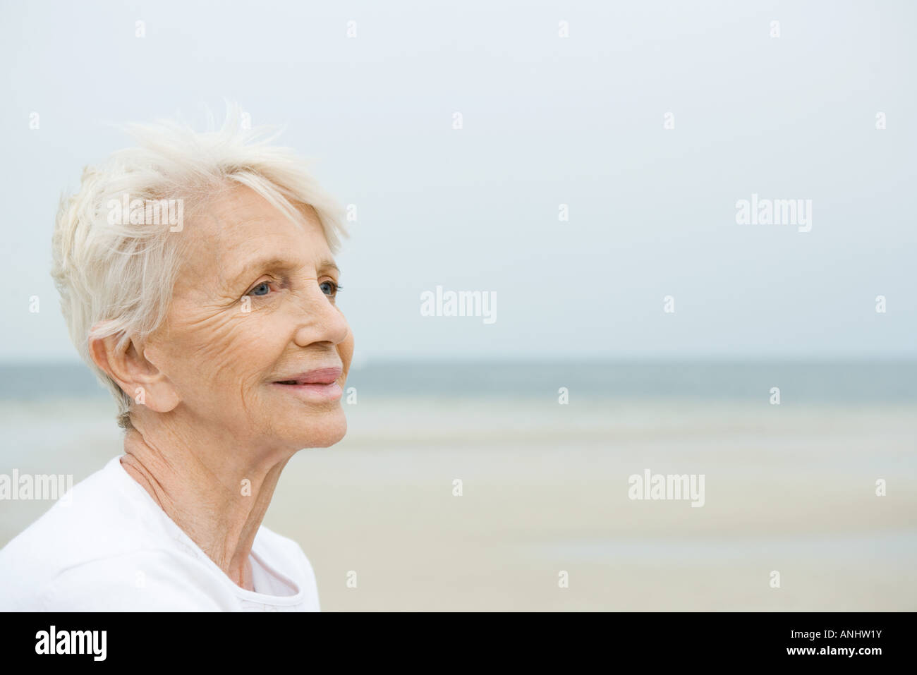 Senior woman smiling, looking away, beach in background - Stock Image