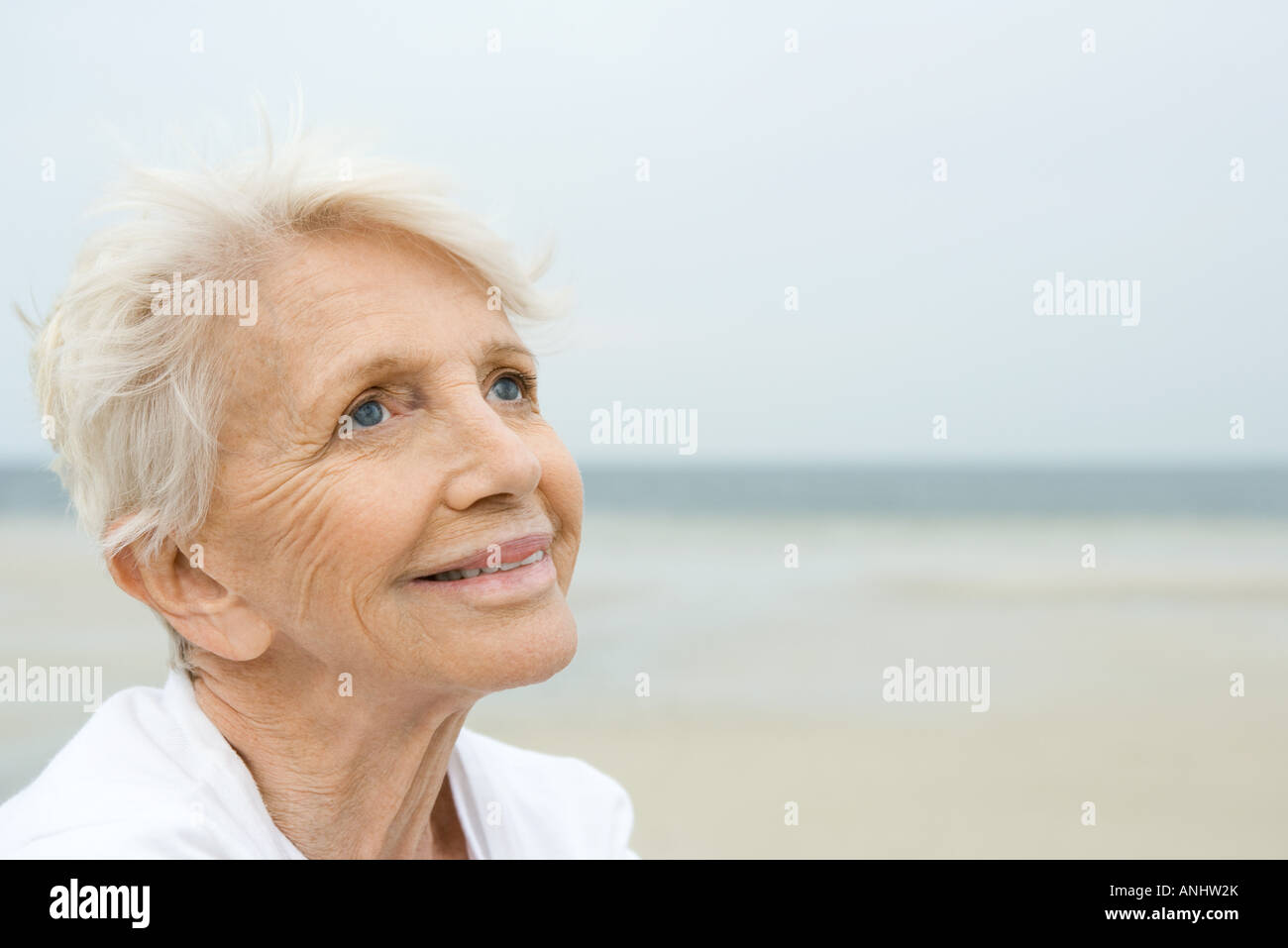 Senior woman smiling, looking up, beach in background - Stock Image