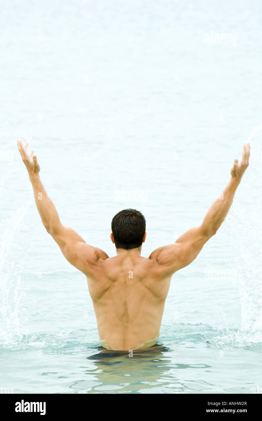 Muscular man raising arms out of water, rear view - Stock Image