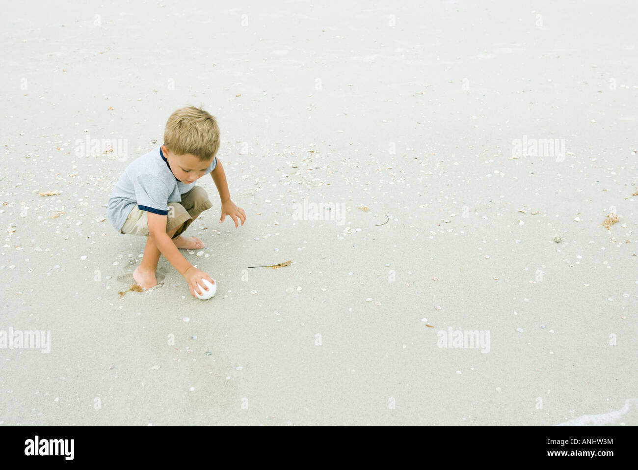 Little boy squatting, picking up ball on beach, full length - Stock Image