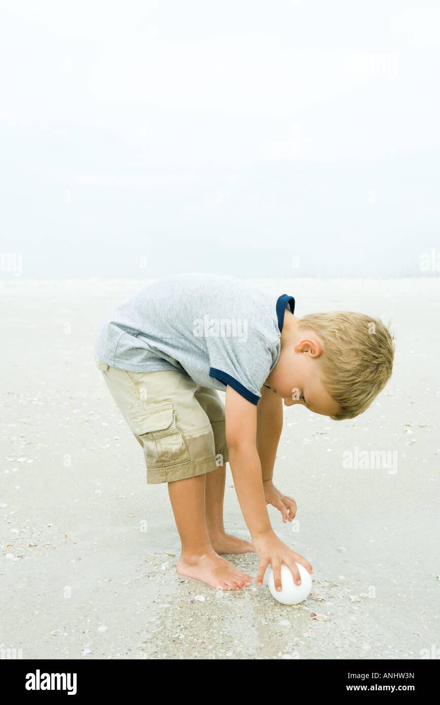 Little boy bending over to pick up ball on beach, full length - Stock Image