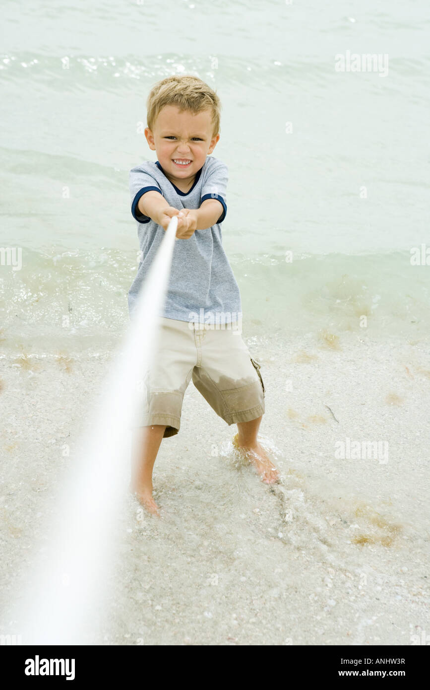 Little boy pulling on rope, making face, on beach - Stock Image