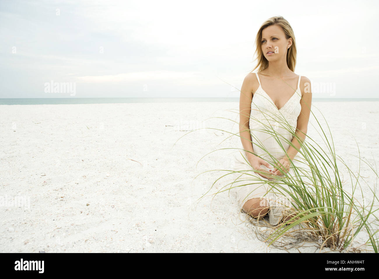 Woman kneeling on beach by dune grass, looking away, full length - Stock Image