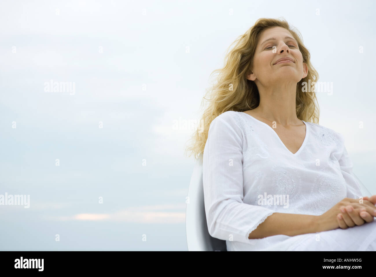 Woman sitting with eyes closed, smiling, sky in background, low angle view - Stock Image