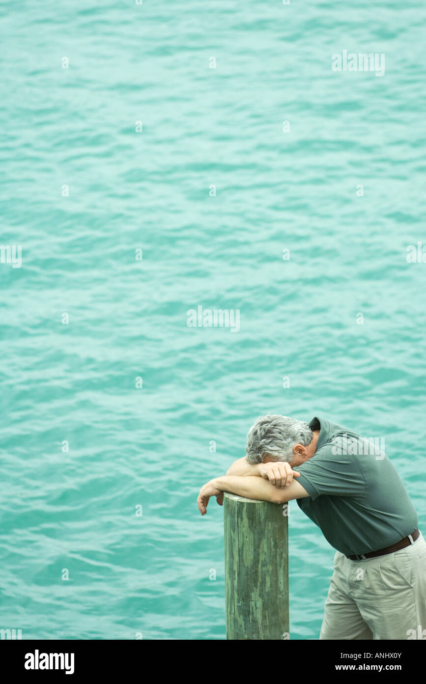 Man leaning on post, head down on arms, high angle view, water in background - Stock Image