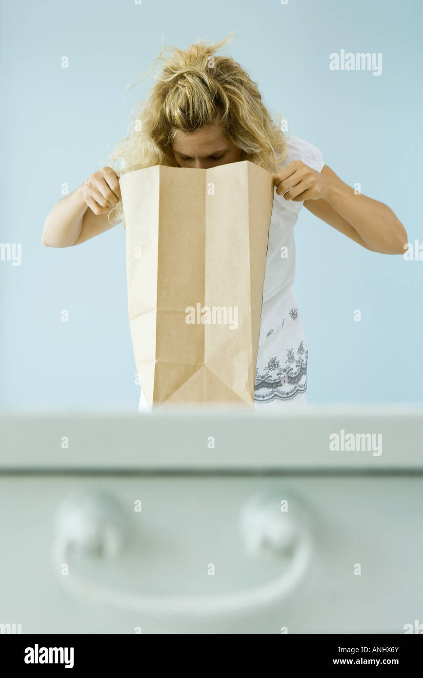 Woman looking into paper grocery bag - Stock Image