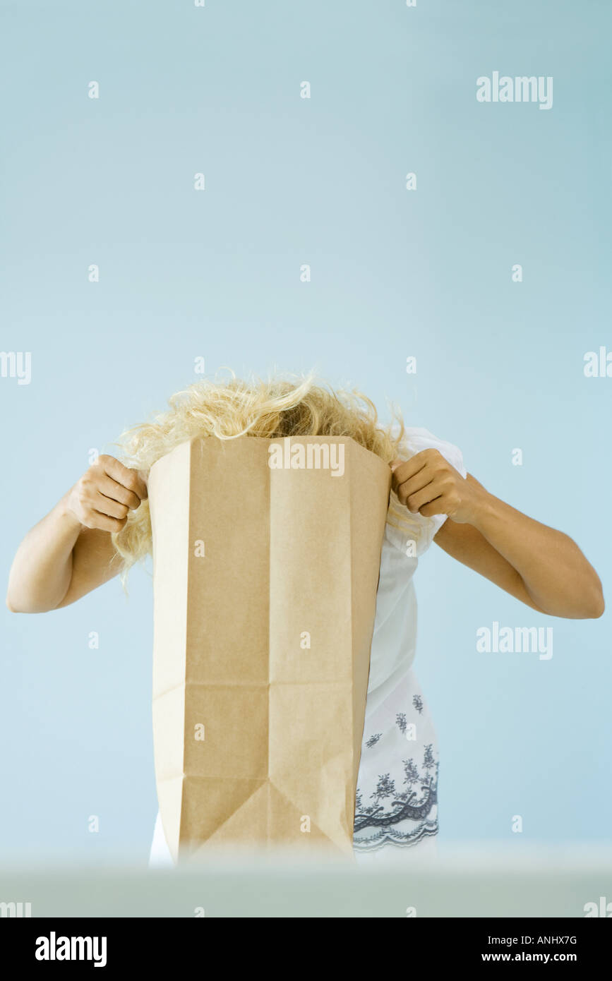 Woman putting head into paper grocery bag - Stock Image