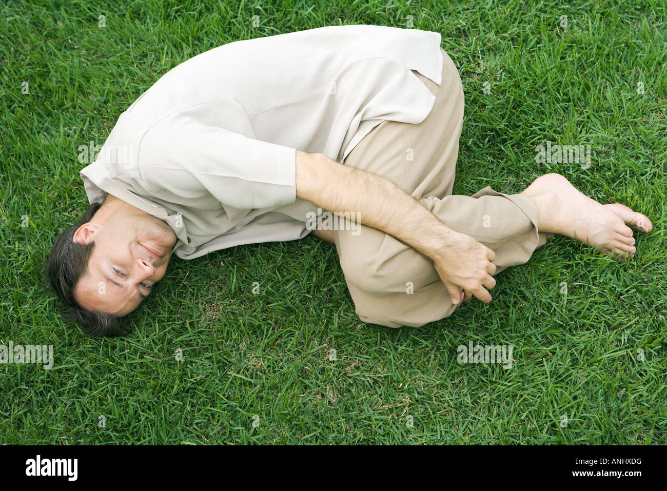 Man lying in fetal position on grass, smiling up at camera - Stock Image