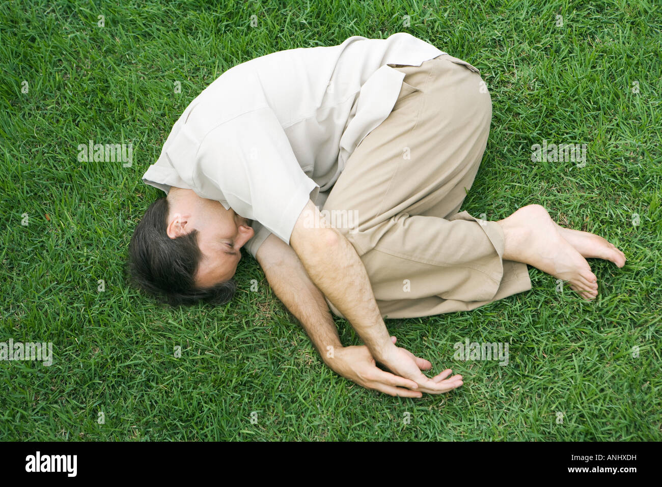 Man lying in fetal position on grass, eyes closed, high angle view - Stock Image
