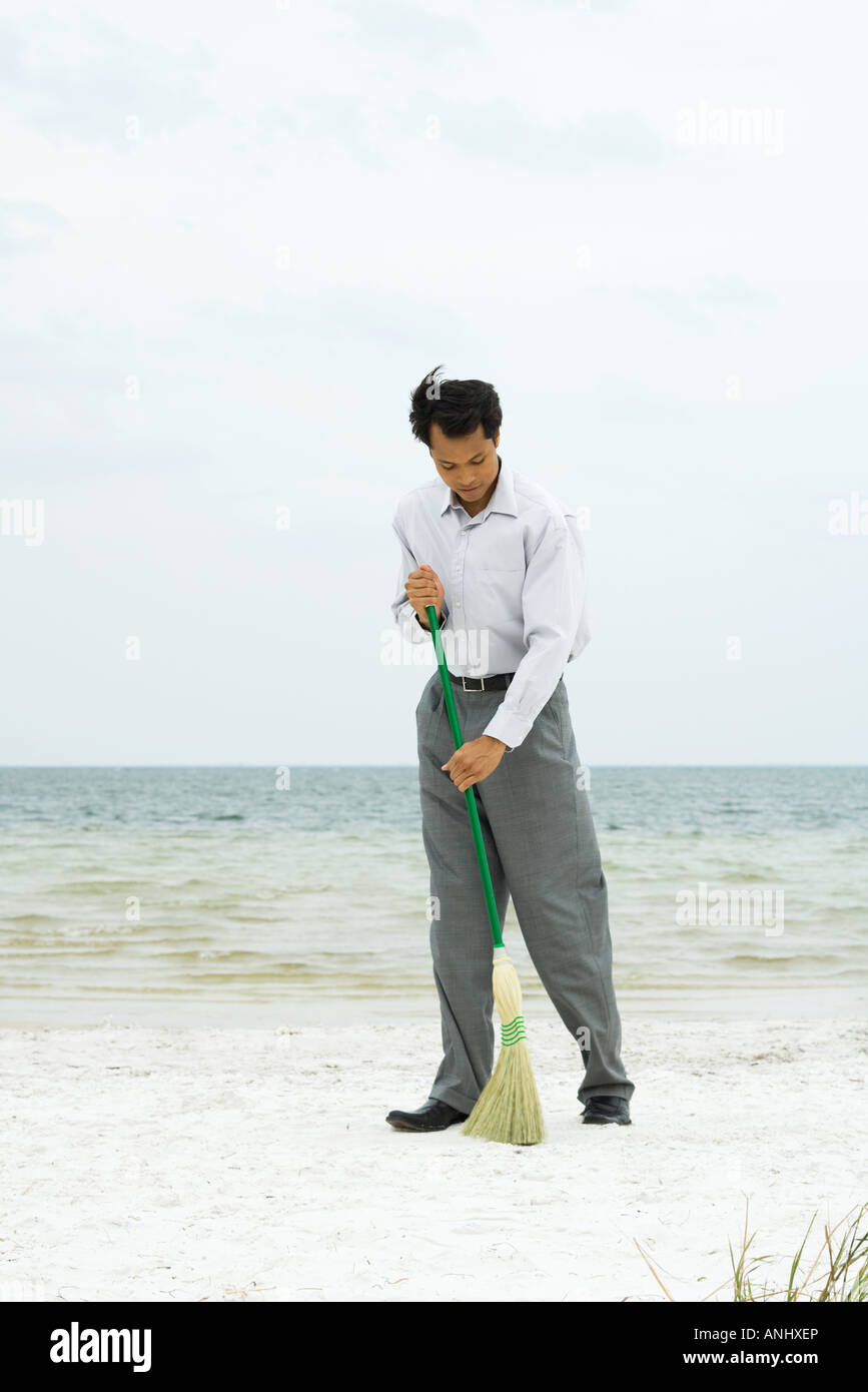 Man standing on beach sweeping with broom, full length - Stock Image