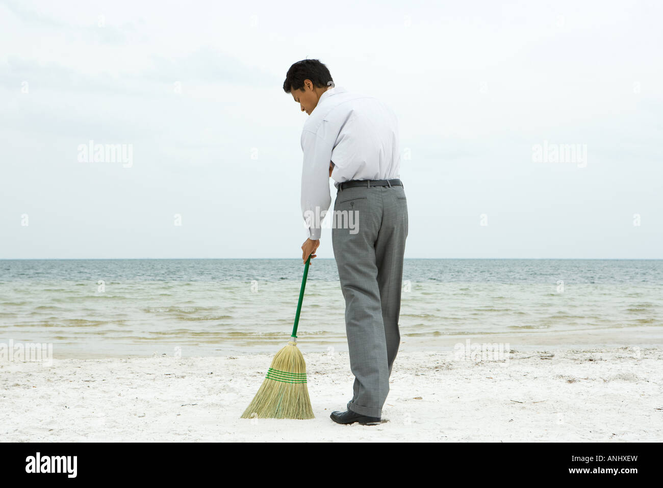 Man standing on beach sweeping with broom, rear view - Stock Image