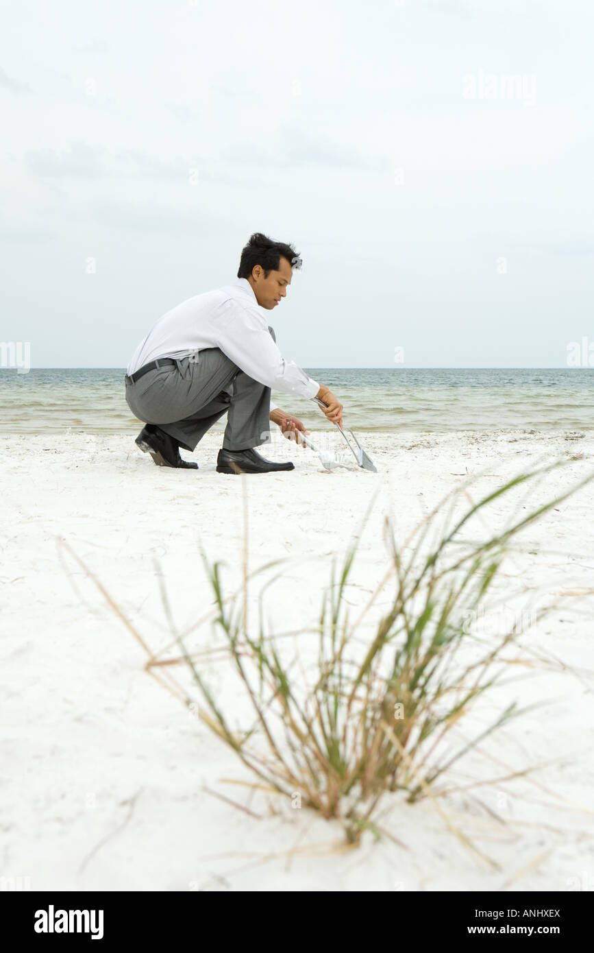 Man crouching on beach, sweeping sand into dustpan, side view Stock Photo
