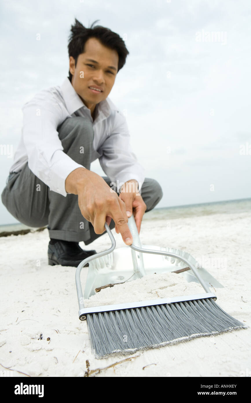 Man crouching on beach, sweeping sand into dustpan, looking at camera, low angle view Stock Photo