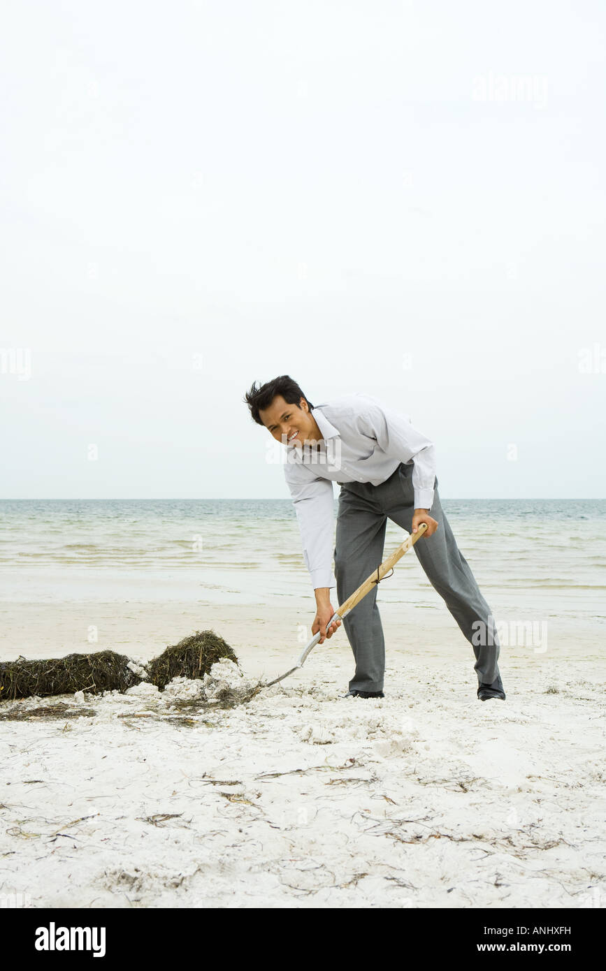 Man at the beach scooping sand with shovel, smiling at camera, full length - Stock Image