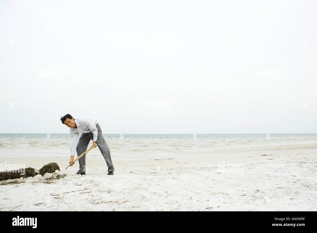 Man at the beach, bending over and digging in sand, smiling at camera Stock Photo