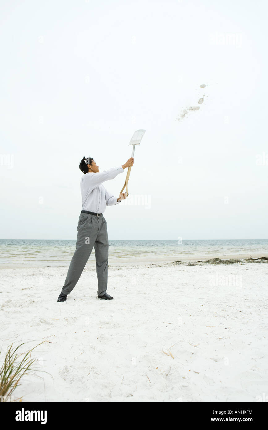 Man at the beach holding up shovel, throwing sand, full length - Stock Image