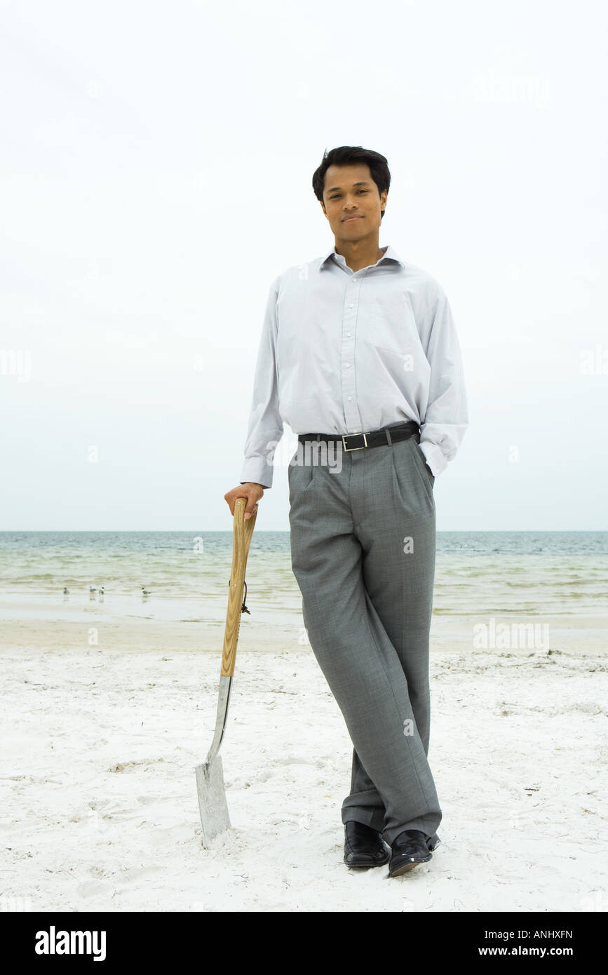 Man standing at the beach, leaning against shovel, smiling at camera - Stock Image