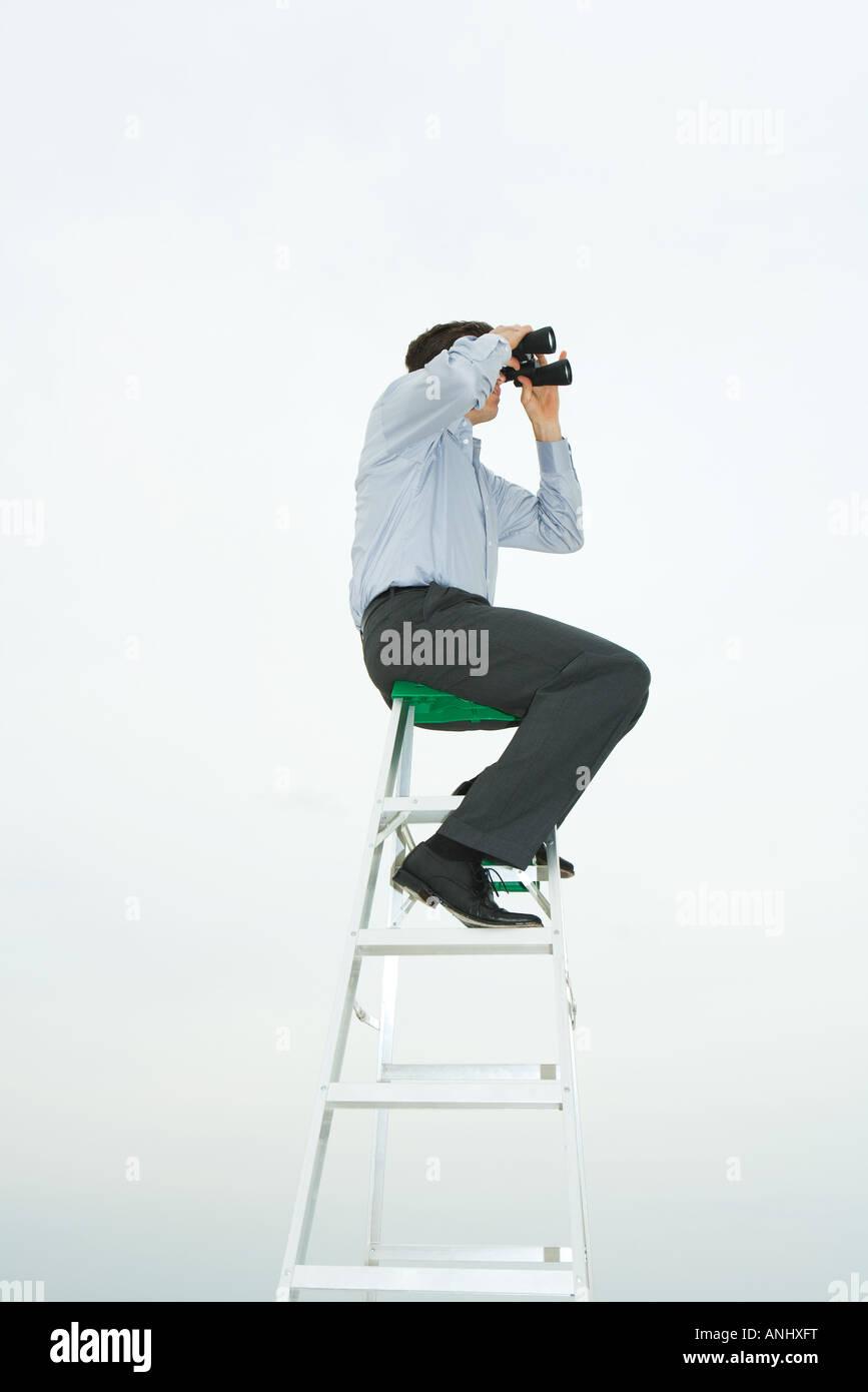 Man sitting on top of ladder looking through binoculars, side view - Stock Image
