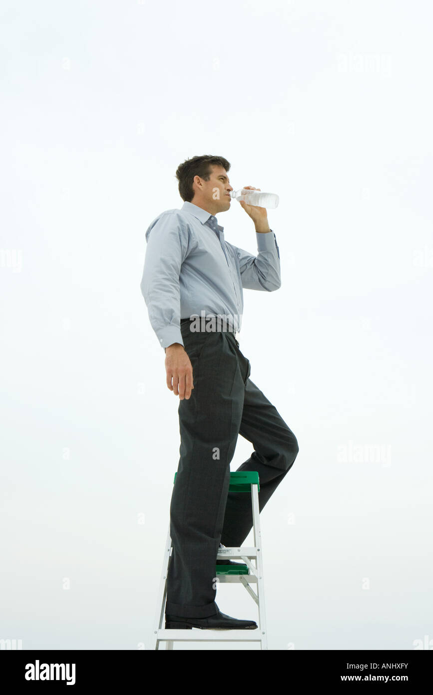 Man standing on top of ladder, drinking bottled water, side view - Stock Image