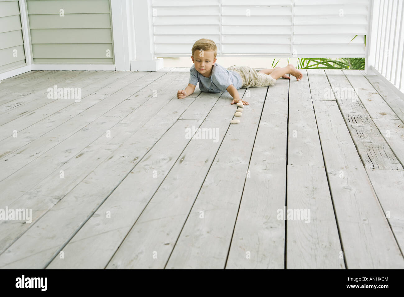Boy lying on stomach on the ground, lining up pebbles - Stock Image