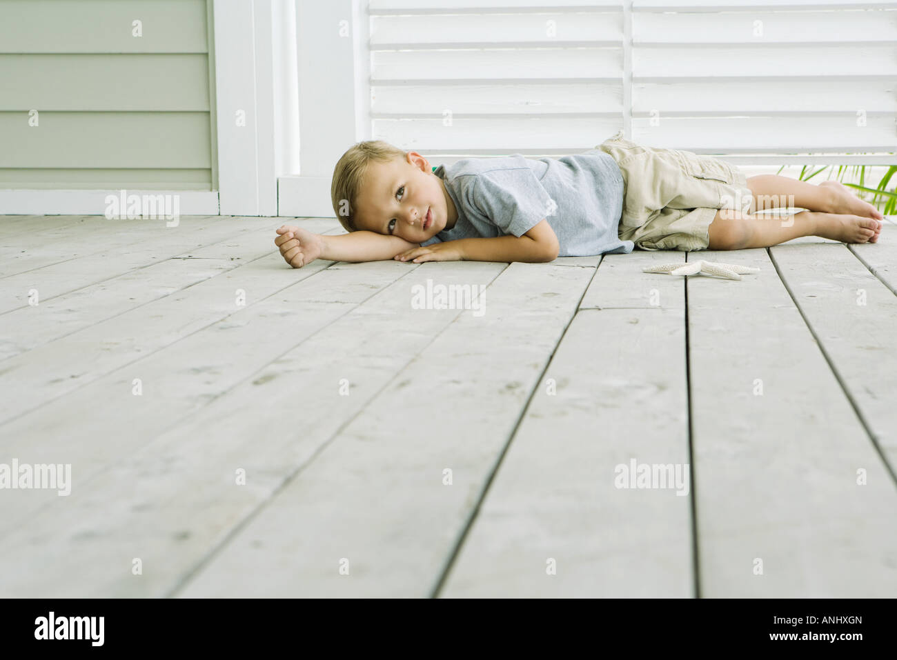 Boy lying on the ground next to starfish, head resting on arm - Stock Image