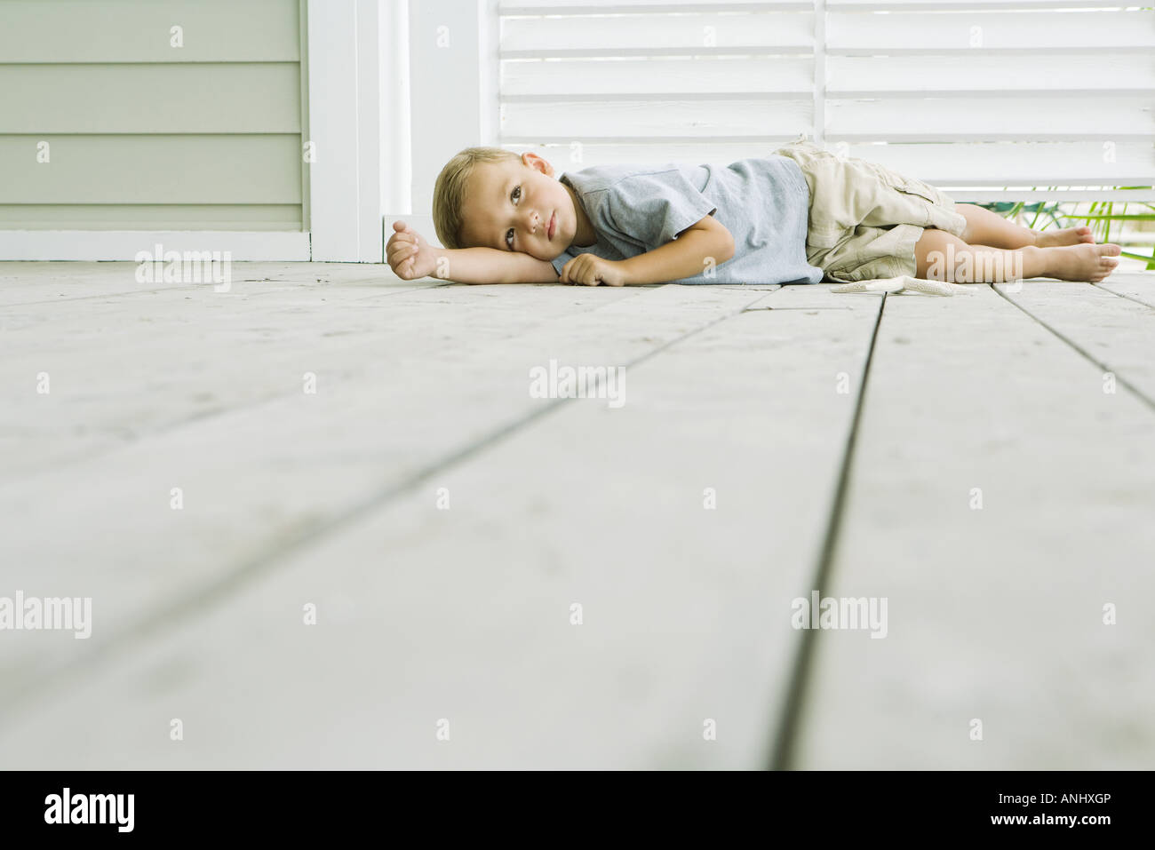 Boy lying on the ground next to starfish, head resting on arm Stock Photo