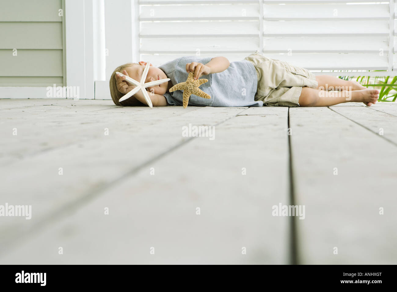 Boy lying on the ground holding two starfish - Stock Image