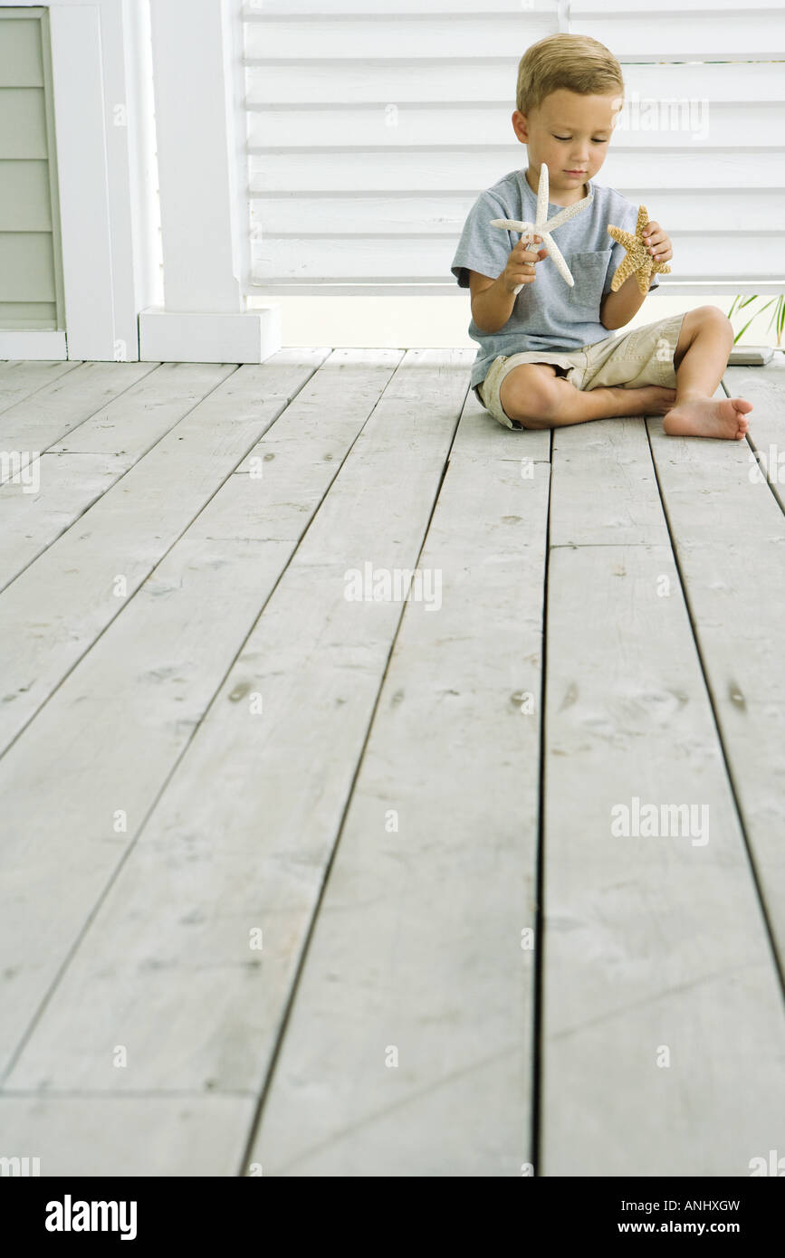 Boy sitting on the ground, holding starfish in each hand - Stock Image