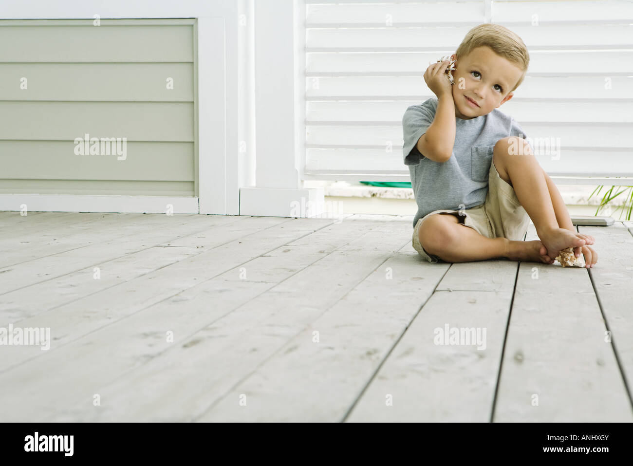 Boy sitting on the ground listening to seashell, smiling - Stock Image