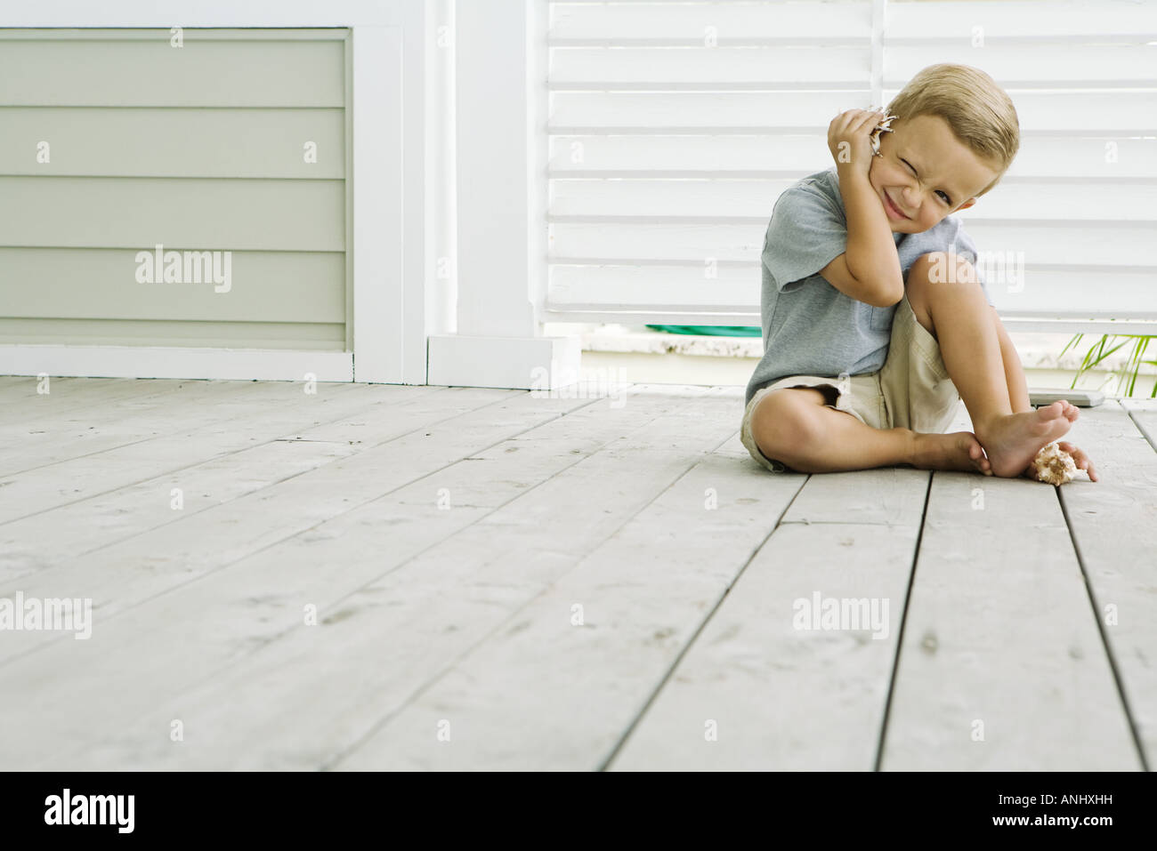 Boy sitting on the ground listening to seashell, squinting at camera, smiling - Stock Image