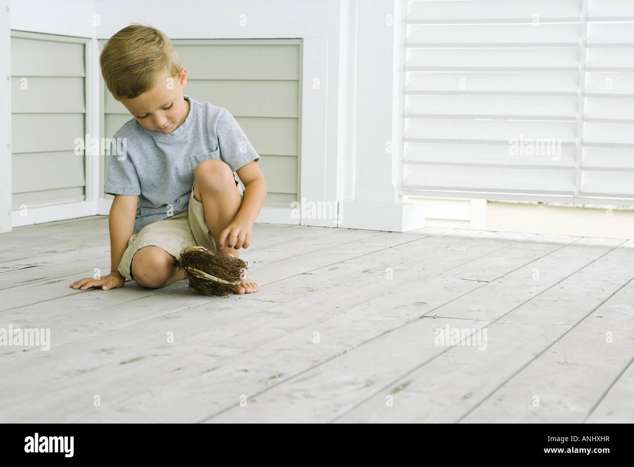 Boy crouching on the ground, touching bird's nest, looking down - Stock Image