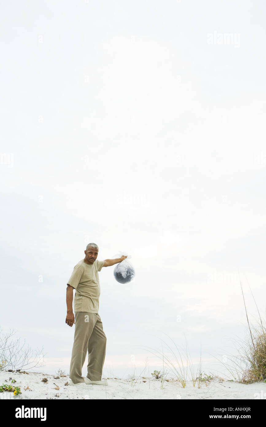 Man holding globe in plastic bag, looking at camera, mid-distance - Stock Image