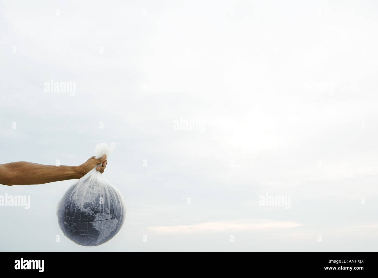 Man holding globe in plastic bag, cropped view - Stock Image