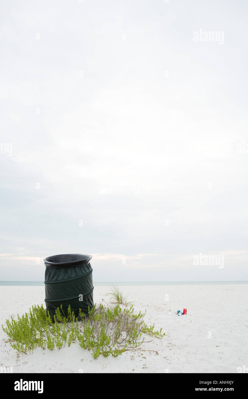 Garbage can on beach, litter lying on the ground nearby - Stock Image