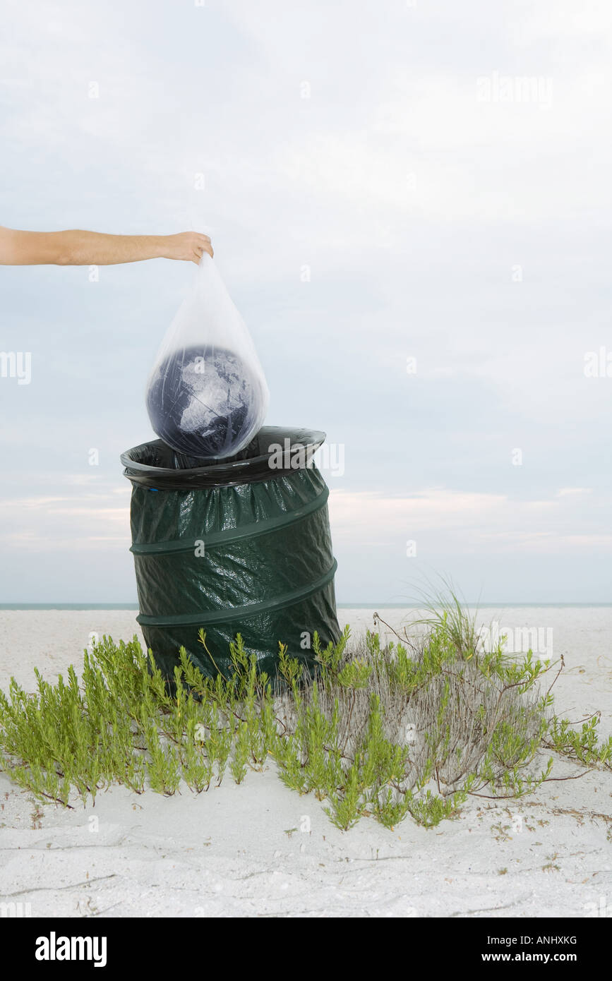 Person holding globe in plastic bag over garbage can, cropped view - Stock Image