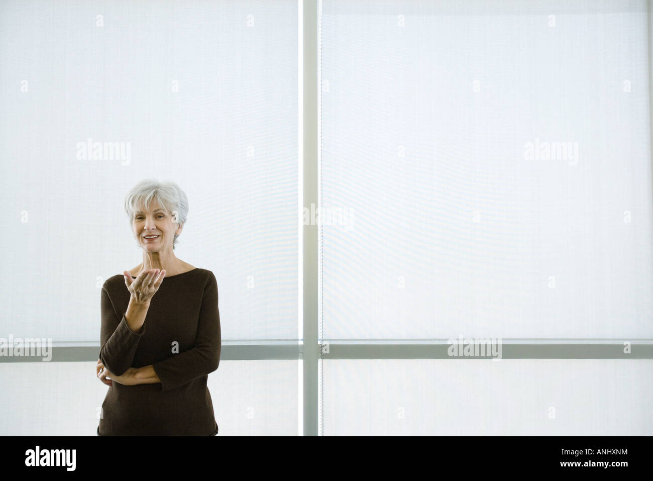 Senior woman standing with hand out, smiling at camera - Stock Image