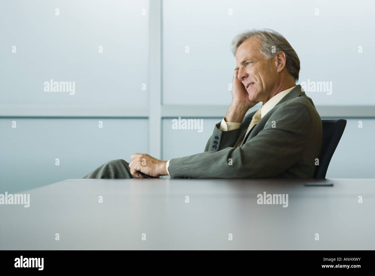 Businessman seated, holding head, looking away - Stock Image