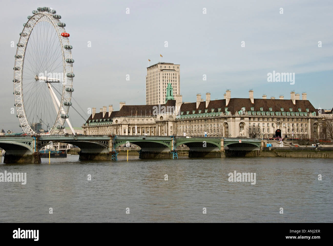 The London Eye and the old County Hall building, with the Shell Tower in the background, seen from across the River - Stock Image