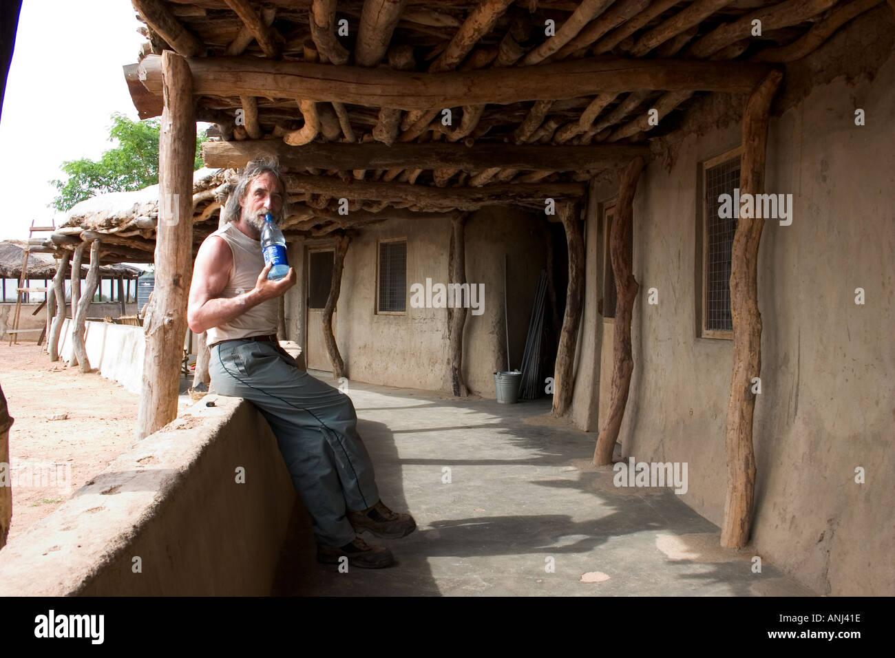 Tourist on the veranda of the lodge Wechiau Hippo Sanctuary northwestern Ghana Community Eco Tourism venture - Stock Image