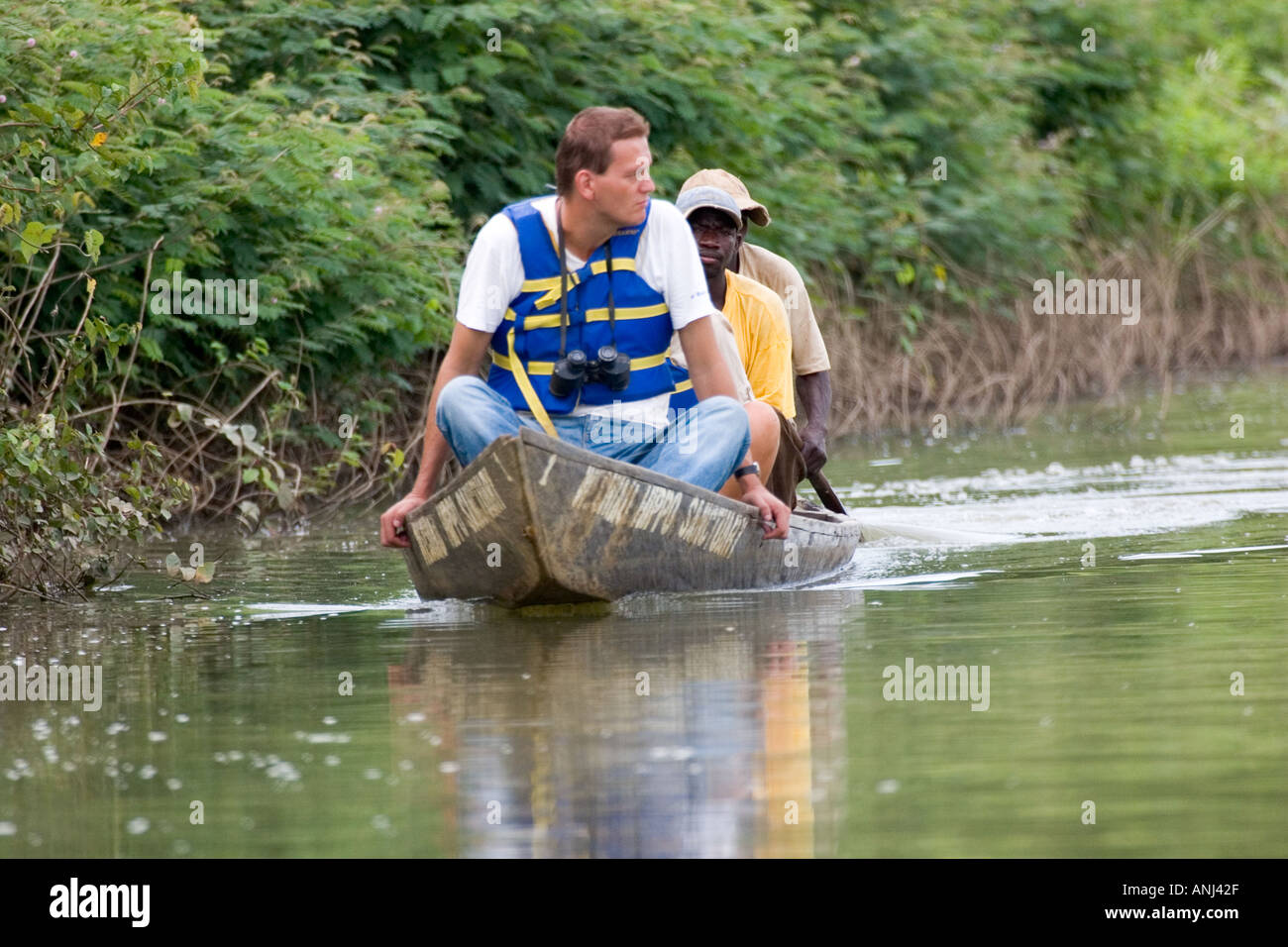 Tourist being canoed down the Black Volta river to see hippos at the Hippo Sanctuary Wechiau - Stock Image