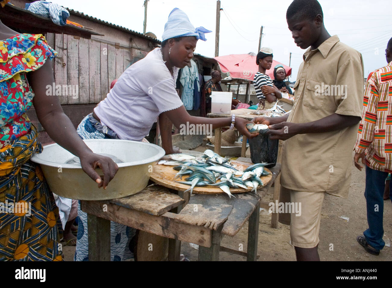 Market woman with customer in a small fishing market in the fishing quarter of Winneba Ghana - Stock Image
