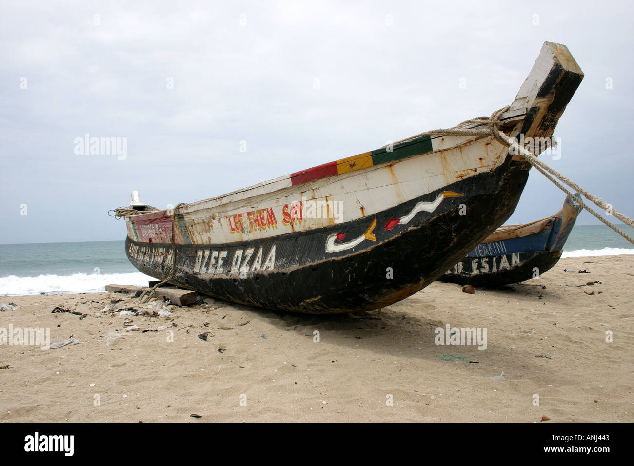 Seagoing dugout canoe parked on beach in between fishing trips Winneba Ghana - Stock Image
